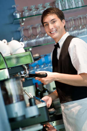 A young and attractive barista making a coffee in an indoor restaurant