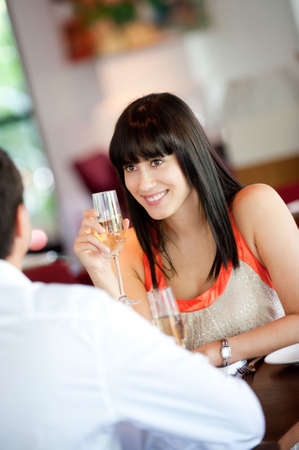 An attractive young woman holding a glass of white wine and smiling at her partner at a restaurant photo