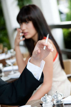 avoid: A young and attractive woman covers her nose to avoid the smoke from a cigarette at an outdoor dining area