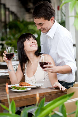A young and attractive woman is surprised by her partner while dining in an outdoor restaurant photo