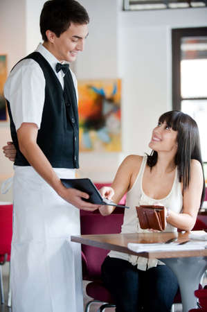 bill payment: A young and attractive woman paying the bill at a restaurant