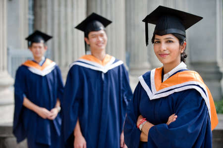 graduating: Three young graduates standing outdoors in graduate attire Stock Photo