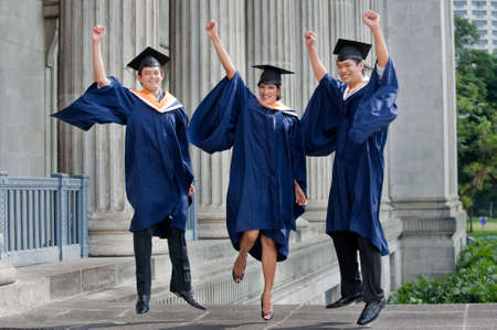 Three young graduates pump their fists in the air outdoors and celebrate their achievement photo