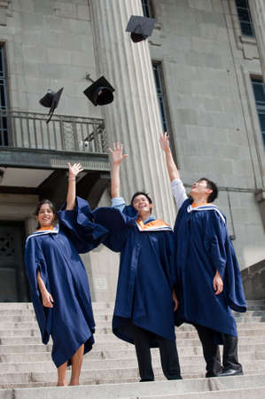A group of graduates toss their mortar boards into the air photo