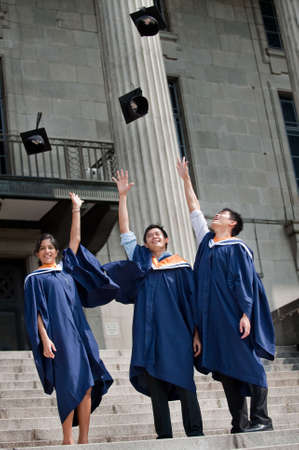 graduating: A group of graduates toss their mortar boards into the air