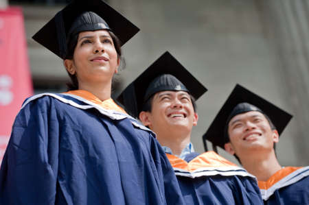 Three young graduates standing outdoors in graduate attire Stock Photo