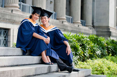 Two young graduates sitting on steps outdoors in graduate attire photo