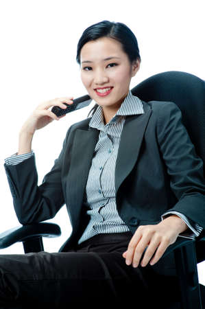 An attractive Asian businesswoman with a phone on white background photo