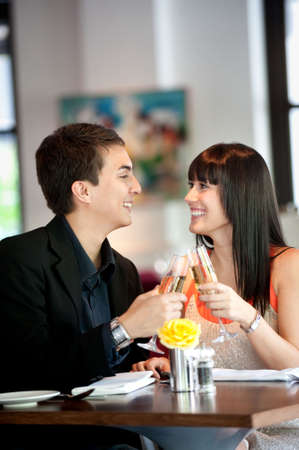 An attractive young couple toasting with white wine in a restaurant Stock Photo - 5341032