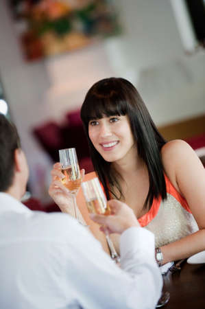 An attractive young woman holding a glass of white wine and smiling at her partner at a restaurant Stock Photo - 5341029