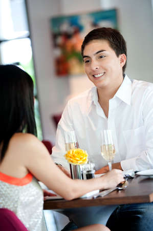 An attractive young man talking to his partner at a restaurant Stock Photo - 5341022