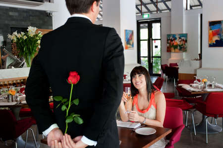 A young and attractive man holding a rose behind his back to surprise his partner in a restaurant Stock Photo - 5341021