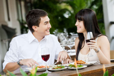 dining: An attractive young couple shares a salad at an outdoor restaurant