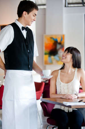 uniform attire: A young and attractive waiter serving coffee to a customer in an indoor restaurant Stock Photo