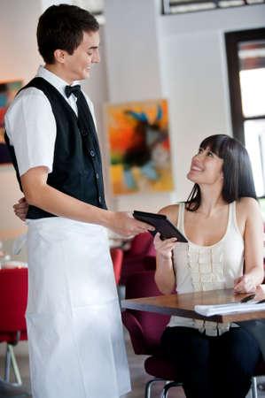 pagando: Una joven y atractiva mujer de pagar la cuenta en un restaurante