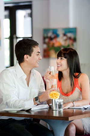An attractive young couple toasting with white wine in a restaurant Stock Photo - 5406382