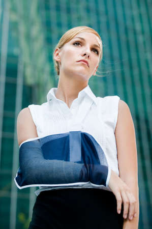broken arm: A young businesswoman with injured arm standing in the city
