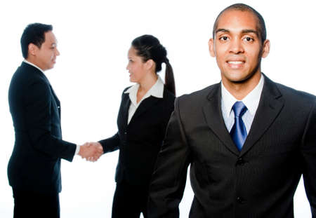 A young businessman standing in front of two colleagues shaking hands photo