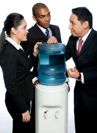 gossip: Drie collega's staan rond een waterkoeler geroddel Stockfoto