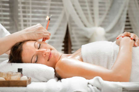 Ear candling being carried out on an attractive caucasian woman in a spa