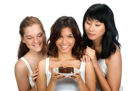A teenager holding a piece of cake as her two friends look at it over her shoulder, against white background photo