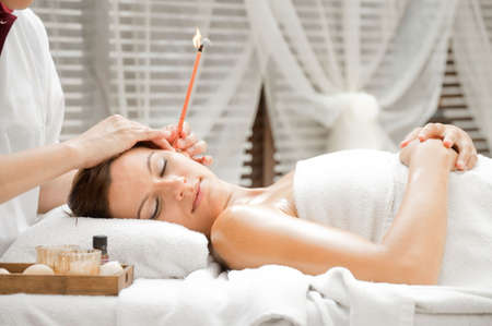 Ear candling being carried out on an attractive caucasian woman in a spa Stock Photo - 5509148
