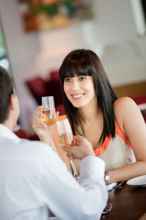 An attractive young woman holding a glass of white wine and smiling at her partner at a restaurant Stock Photo - 5527402