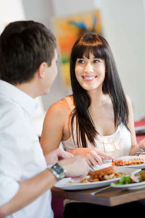 A young and attractive woman dining with her partner in an indoor restaurant photo
