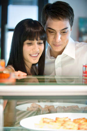 A young and attractive couple looking at dishes arranged behind a counter photo