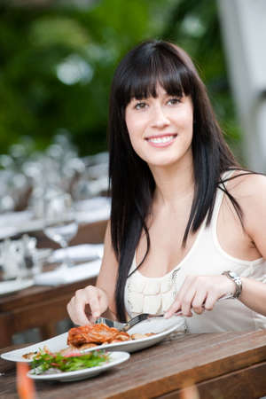alfresco: A young and attractive woman having a meal in an outdoor restaurant
