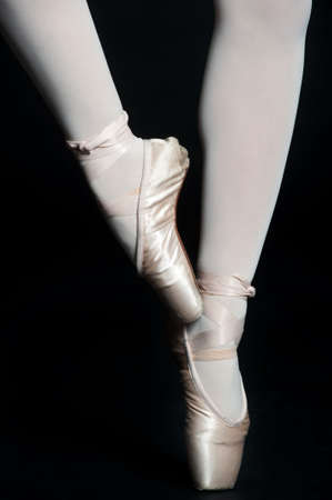 ballet shoes: A pair of slender ballerina legs on tip toe against black background