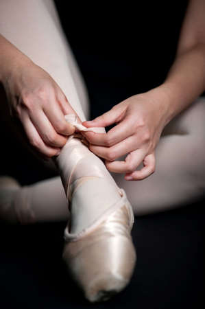 Close up of a ballerina tying her ballet shoes against black background photo