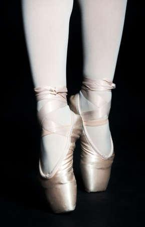 zapatillas ballet: Un par de pies con zapatillas de ballet de pie en puntas de pie, sobre fondo negro Foto de archivo