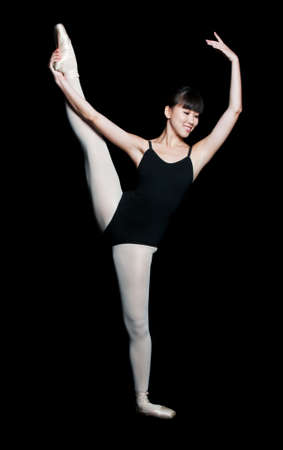 leotard: A young asian female ballerina does a ballet pose against black background