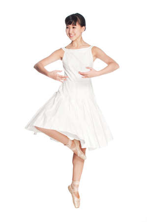 pirouette: A young asian ballerina doing a pirouette against white background