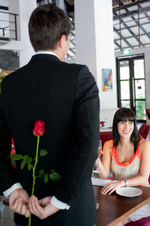 A young and attractive man holding a rose behind his back to surprise his partner in a restaurant photo