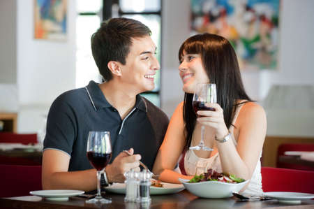 A young and attractive couple dining together in an indoor restaurant photo