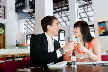 An attractive young couple toasting with white wine in a restaurant Stock Photo - 5680739