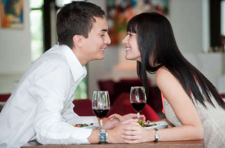 A young and attractive couple holding hands and about to kiss over their dinner in an indoor restaurant photo