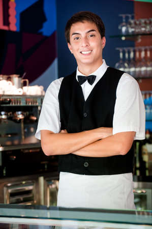 A young and attractive waiter stands behind the bar in an indoor restaurant Stock Photo - 5680741