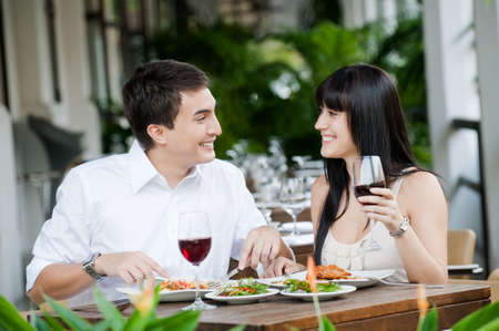 An attractive young couple shares a salad at an outdoor restaurant photo