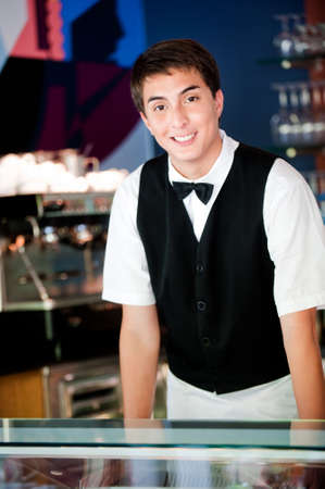 barista: A young and attractive waiter stands behind the bar in an indoor restaurant