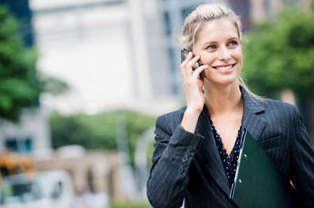 A young and attractive businesswoman using her mobile phone and holding a file under her arm Stock Photo - 5705460