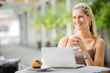 A young attractive caucasian woman uses a laptop outdoors at a cafeteria Stock Photo - 5705459