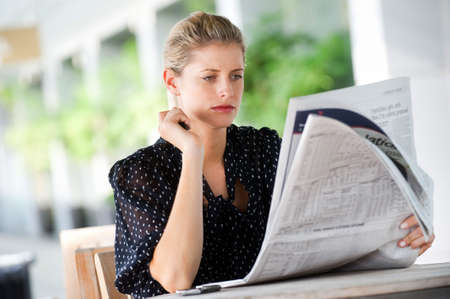 A young attractive woman reading newspapers at a cafeteria Stock Photo - 5705447