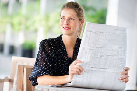 A young attractive woman reading newspapers at a cafeteria Stock Photo - 5705442