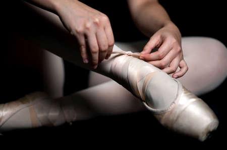 zapatillas ballet: Una bailarina atar las zapatillas de ballet en contra fondo negro