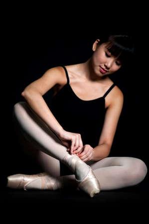 ballet slippers: A ballerina tying her ballet slippers on, against black background