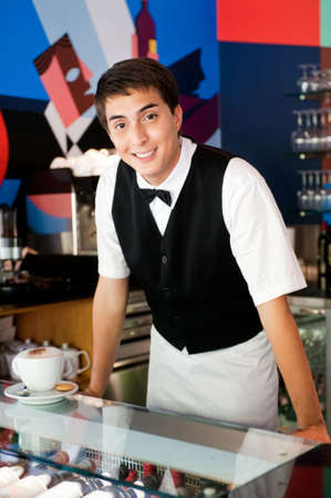 A young and attractive waiter stands behind the bar in an indoor restaurant with a cup of coffee photo
