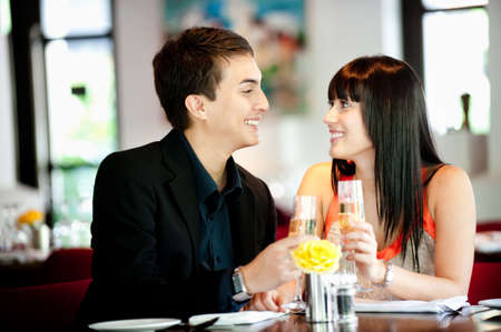 An attractive young couple toasting with white wine in a restaurant Stock Photo - 5748694